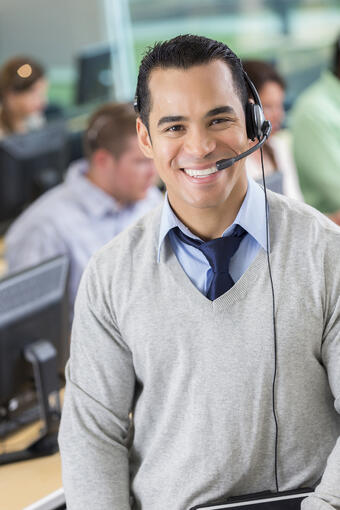 White male hotline employee with headset  smiling